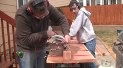 Man and boy sawing from end Stock Footage