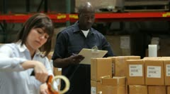 Worker Checks Clipboard As Colleague Seals Boxes Stock Footage