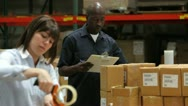 Stock Video Footage of Worker Checks Clipboard As Colleague Seals Boxes