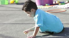 Boy Playing In Playground With Chalk Stock Footage