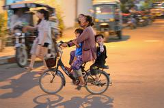 Stock Photo of mother with two children riding bicycle in Laos