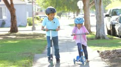Two Children Riding Scooters Towards Camera Stock Footage