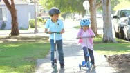 Stock Video Footage of Two Children Riding Scooters Towards Camera