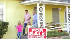 Family Standing By For Sale Sign Outside Home Stock Footage