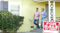 Couple Standing By For Sale Sign Outside Home - stock footage