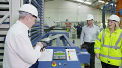 Mature factory manager shows his staff how to operate machinery Stock Footage