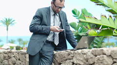 Angry businessman in tourist resort talking on cellphone, steadicam shot Stock Footage