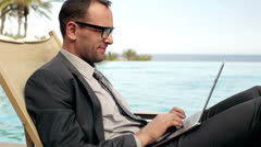 Businessman working on laptop in tourist resort, steadicam shot Stock Footage