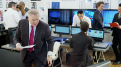 Diverse team of financial traders at work in a busy office - stock footage