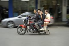 Stock Photo of four chinese persons riding motorcycle