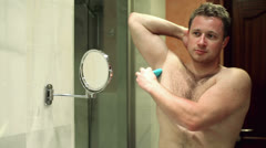Man takes care of his hygiene by applying deodorant to his  armpit - stock footage