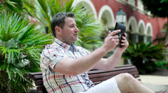 Young man in tourist resort chatting with tablet computer, steadicam shot Stock Footage