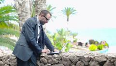 Businessman in tourist resort working on laptop computer, steadicam shot Stock Footage