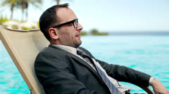 Businessman relaxing on sunbed in tourist resort, steadycam shot Stock Footage