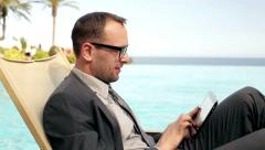 Businessman working with tablet in tourist resort, steadycam shot Stock Footage