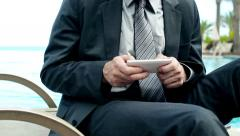 Businessman hands texting sms by the swimming pool, steadycam shot Stock Footage