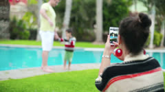Happy family. Mother taking photo by swimming pool, steadicam - stock footage
