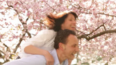 Mature man giving his wife a piggyback ride in spring Stock Footage