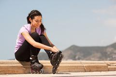 Girl going rollerblading sitting putting on inline skates Stock Photos