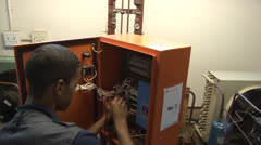 Student african black Electrical Testing of a  DB Box NTSC - stock footage