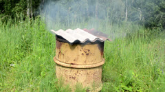 Smoke rises rusty smokehouse barrel asbestine slate roof Stock Footage
