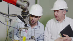Mature male factory manager explains to younger man how the machinery works Stock Footage