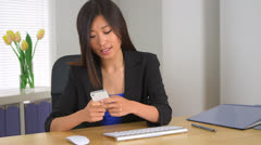 Chinese businesswoman texting at desk Stock Footage