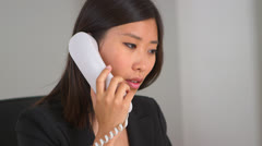 Chinese businesswoman discussing issues through the phone - stock footage