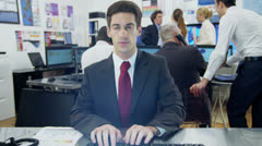Young businessman working at his desk from the pov of the computer screen - stock footage