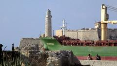 Cargo ship leaving Havana, Cuba, with castle and lighthouse Stock Footage
