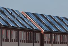 a new row of townhouses with solar panels attached - stock photo