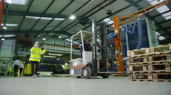 Team of busy warehouse workers lifting and moving empty pallets and boxes Stock Footage