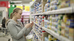 Young woman is choosing food for her child in the shopping center. Stock Footage