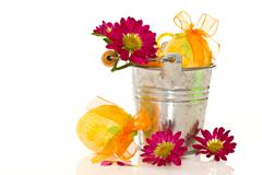 decorative easter eggs in a bucket of flowers - stock photo