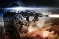 Assault soldier with rifle on apocalyptic clouds, firing Stock Photos