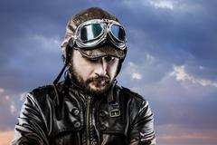 Stock Photo of pilot with glasses and vintage hat with proud expression over cloudscape
