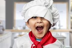 Funny child dressed as a cook Stock Photos