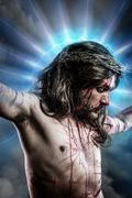 calvary jesus, man bleeding, representation of passion with blue light halo - stock photo