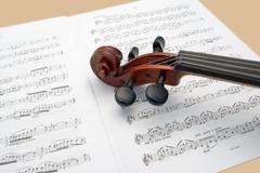 Violin neck resting on sheet music Stock Photos