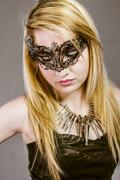 beautiful blonde in black leather jacket, mysterious mask and silver jewelry - stock photo