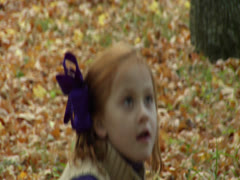 Kid throws the leaves slowly and watches it eagerly Stock Footage