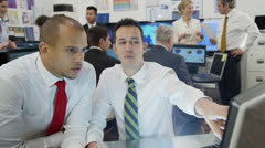 Diverse team of financial traders hard at work in a busy office - stock footage