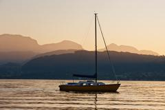 Solitary yacht on the lake in a sunset Stock Photos