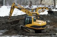 Stock Photo of excavator loader during earthmoving works - dredging the pond