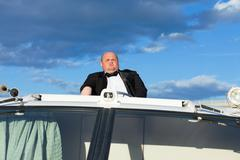 Overweight man in a tuxedo at the helm of a pleasure boat Stock Photos