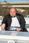 overweight man in a tuxedo at the helm of a pleasure boat - stock photo