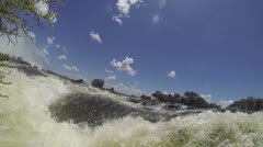 Low angle of water rushing along Zambezi River Stock Footage