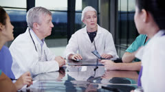 Stock Video Footage of Multi ethnic medical team in a meeting discuss a patient's x-ray results