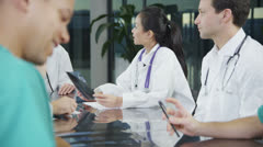 Multi ethnic medical team in a meeting discuss a patient's x-ray results - stock footage