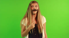 A young woman with green background and the mustache stick Stock Footage